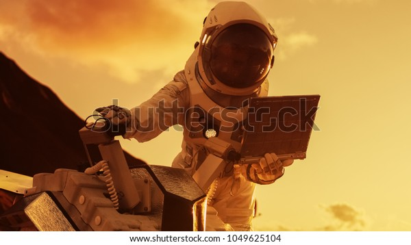 L'astronaute en costume spatial travaille sur ordinateur portable, ajustant Rover sur une nouvelle planète rouge extraterrestre, probablement Mars. Exploration, mission, découverte et colonisation de planètes habitables.