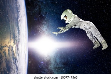 Astronaut in space, in zero gravity near the planet Earth. The concept is to find a new earth. Elements of this image furnished by NASA.