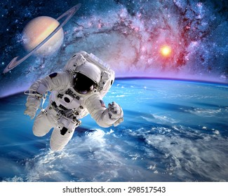 Astronaut spaceman outer space planet saturn earth sun universe. Elements of this image furnished by NASA.