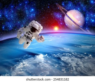 Astronaut spaceman outer space science fiction saturn planet. Elements of this image furnished by NASA.