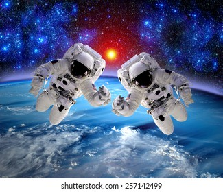 Astronaut spaceman outer space teamwork hands earth people. Elements of this image furnished by NASA.