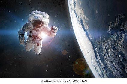 Astronaut at spacewalk. Concept of conquering the universe by the human race. Elements of this image furnished by NASA
