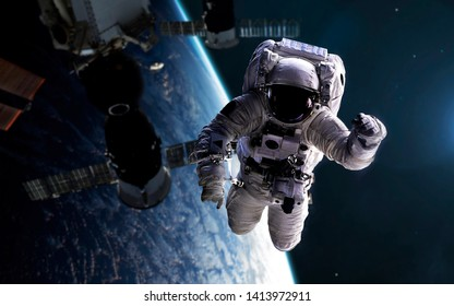 Astronaut at spacewalk with space station at background. Elements of this image furnished by NASA