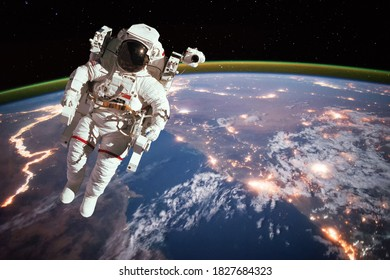 Astronaut walking in space with earth background, at night. Elements of this image furnished by NASA.
