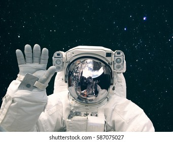 "Astronaut waves with a hand against deep space and stars.  ""The elements of this image furnished by NASA"""
