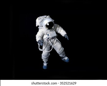 Astronaut wearing a pressure suit against a black background.