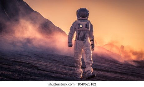 Astronaut Wearing Space Suit Walks on the Red Planet/Venus During Sunset. In the Background His Base with Rover Parked, Hot Red Daylight Sun Shines.