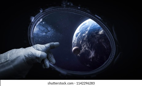 Astronauts hand near porthole of space station. Earth, Moon and galaxy on background. Elements of this image furnished by NASA
