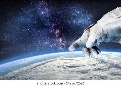 Astronauts hand over the Earth in the space. Civilization and technologies. Elements of this image furnished by NASA