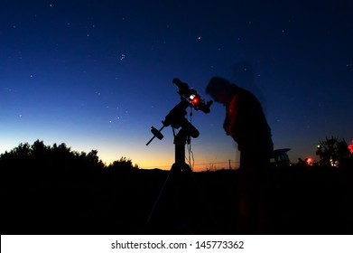 Astronomer in the night with telescope