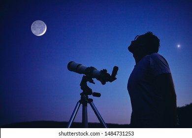 Astronomer with a telescope watching at the stars and Moon. My astronomy work.