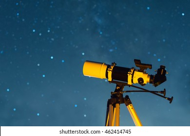 Astronomical Telescope Pointed at the Starry Sky in the Night. Real Equipment and Night Sky. Telescope on Tripod.