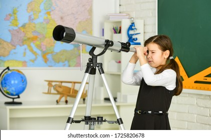 Astronomy and Astrophysics. Stars and galaxies. Study telescope. School astronomy lesson. School girl looking through telescope. Telescope tripod in classroom. School hobby club. Observation concept.