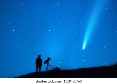 Astronomy lover with a telescope observing a comet in the blue starry sky at night. Silhouette of a person observing the immensity of the universe and the stars. Trace of a comet or a shooting star. - Shutterstock ID 1819408763