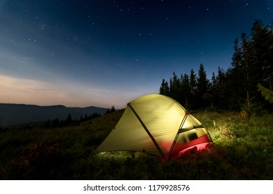 Astrophotography of night camp and starry skies at Carpatian mountains in Ukraine. Green tent on the foreground is highlighted from the inside. Concept of  backpacking travel lifestyle.
