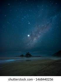 Astrophotography showing the milkway in a beach with a little island in the middle
