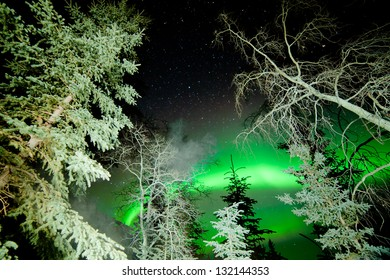 Astrophotography star trails with green glowing display of Northern Lights or Aurora borealis over boreal forest or taiga of Yukon Territory  Canada