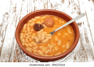 Asturian bean stew in a clay pot on a background of old wood