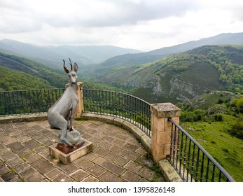 Asturias/Spain - May 10 2018: Look over Asturias lush green fields with a heavy fog sky and a deer statue