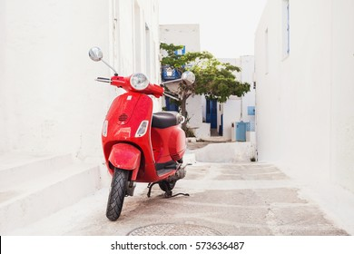 ASTYPALAIA, GREECE - MAY 13, 2016: Red old-fashioned scooter motorbike - greek traditional way of transportation on a picturesque street