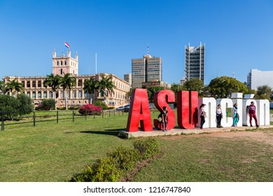 "ASUNCION, PARAGUAY - July 13, 2018: Five tourists are posing with ""ASUnción"" letters and Palacio de los López (Presidential palace) in background. Latin American capital of Asuncion city, Paraguay."