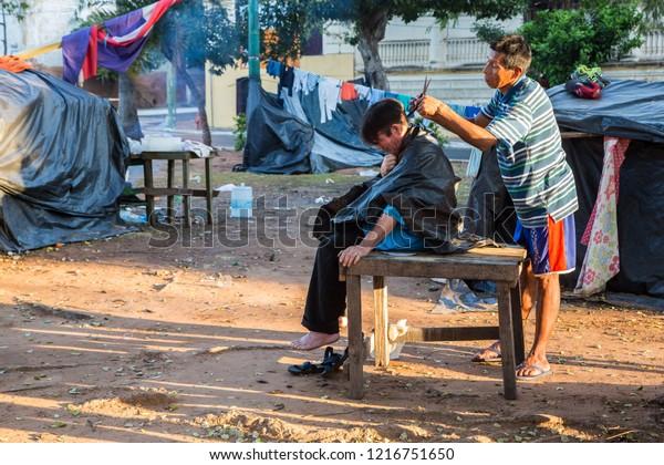 ASUNCION, PARAGUAY - July 13, 2018: Outdoor haircut in slums of Asuncion city. Hairdressing on streets of Ciudad de Asunción Paraguay. Two men, tent camp