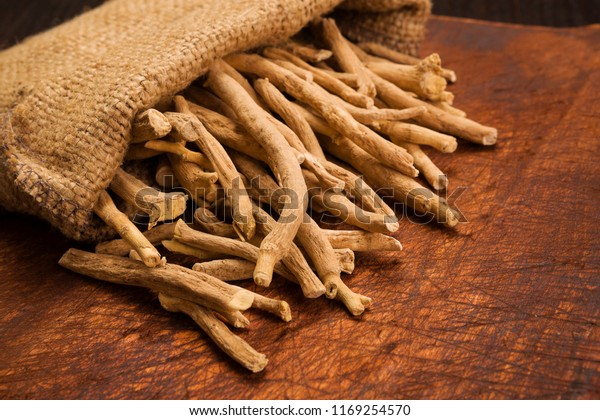 Aswagandha root on wooden table. Herbal adaptogen medicine.
