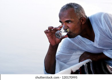 ASWAN - APRIL 28:Egyptian man drink waters from the nail river in Aswan, Egypt on April 28 2007.The Nile river provides nearly all of Egypt's fresh water.