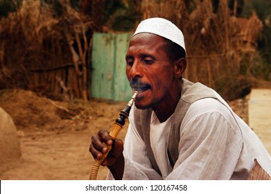 ASWAN - APRIL 30 2007:Egyptian Nubian man smoke from a shisha pipe in a village in Aswan,Egypt. Nubians are the people settling along the banks of the Nile from northern Sudan to Aswan.