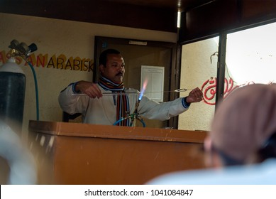 Aswan, Egypt. February 17, 2017: Egyptian artisan worker located at the door of a perfume factory in Aswan molding glass