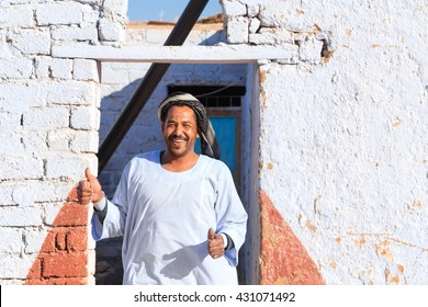 ASWAN, EGYPT - FEBRUARY 7, 2016: Nubian man wearing traditional clothing standing in front of the house.