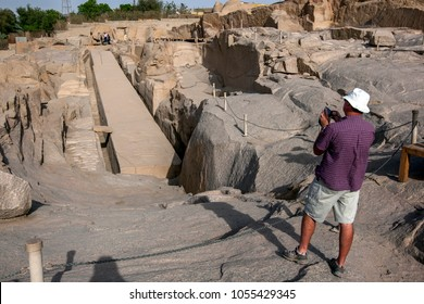 ASWAN, EGYPT - MARCH 19, 2010 : A tourist takes a photograph of the Unfinished Obelisk at the ancient Western Quarry near Aswan in Egypt. The obelisk was being constructed for the Pharaoh Seti I.