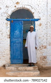 ASWAN, EGYPT - MARCH 20, 2010 : An Egyptian man stands at the entrance to his house in the Nubian village of Garb-Sohel in the Aswan region of Egypt.