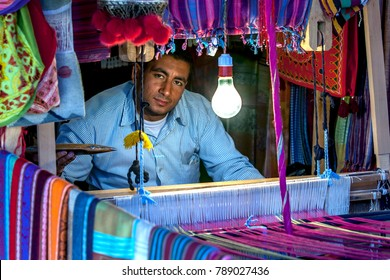 ASWAN, EGYPT - MARCH 20, 2010 : A man operating a weaving loom in the Nubian village of Garb-Sohel in the Aswan region of Egypt. Hand made textiles made in Egypt are of exceptional quality.