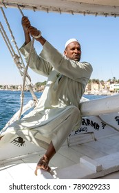 ASWAN, EGYPT - MARCH 20, 2010 : A felucca captain adjusts the sails of his boat whilst sailing down the River Nile in the Aswan region of Egypt.