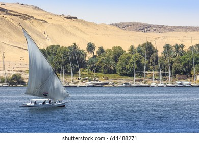 ASWAN, EGYPT - MARCH 25, 2017: Felucca (river boat) on the Nile, with the Sahara behind in Aswan, Egipt.