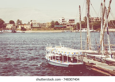 ASWAN, EGYPT - MARCH 25, 2017:Wooden boats carrying passengers docked along the Nile River in Aswan, Egypt, North Africa