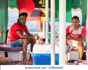 Aswan, Egypt - September 13, 2018: Egyptian men smoking shisha pipe while sail in a touristic motorboat in Nile river