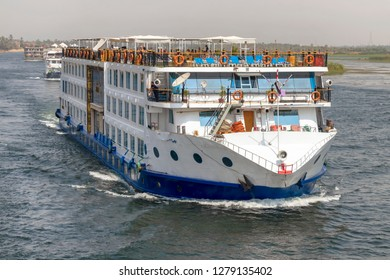 Aswan, Egypt - September 16, 2018: Floating hotels (tourist boats) motor down the River Nile towards Aswan in central Egypt. The tourist boats cruise between Luxor and Aswan in Upper Egypt
