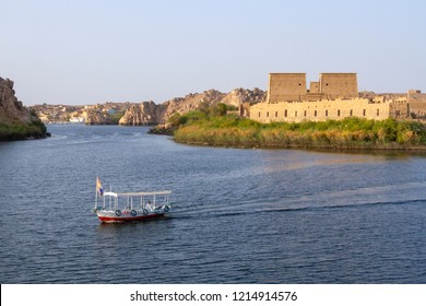 Aswan - Egypt / September 2018: boat crossing the Nile river with philae temple at the background.