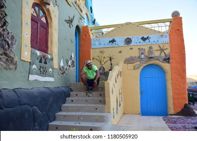 Aswan/Egypt - 12/15/2016 - the colorful houses of nubian Egyptians and model siting infront of it .