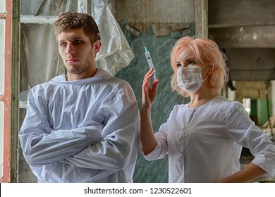 Asylum nurse or doctor in mask with a syringe in hand is preparing to give an injection to an insane psycho patient in a straitjacket
