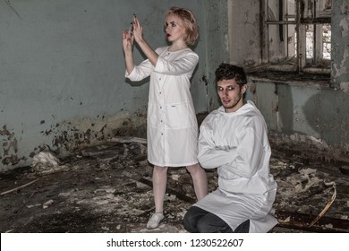 Asylum nurse or doctor with a syringe in hand is preparing to give an injection to an insane psycho patient in a straitjacket, inside of abandoned ruined hospital. Some horror movie scene