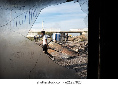 A asylum seekers walks past the smashed window of a burnt out shop during the evacuation of the Jungle camp, Calais, France. October 2016