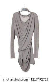 asymmetrical model of female garment, asymmetric grey blouse, gray cotton tunic is on white baground, isolated blouse is as single object, extravagant clothes, draped long sleeve shirt is  on hanger