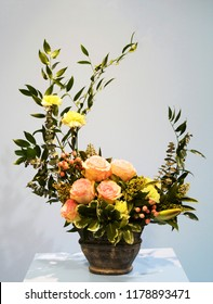 An asymmetrical spring floral arrangement of coral roses and yellow carnations.
