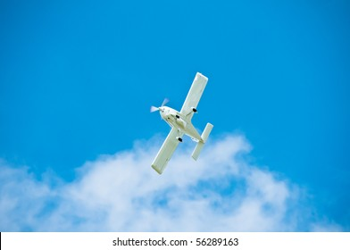 AT-3 type airplane flying through sky with clouds