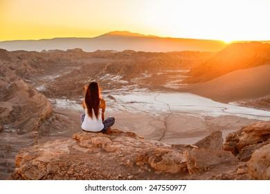 ATACAMA DESERT, CHILE - NOV 3, 2014: Unidentified girl sits on the sunset in the Atacama desert, Chile. Atacama Desert proper occupies 105,000 square kilometres