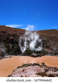 Atacama Highlands thermal area in Chile - view of steam rising from hillside with the sulphurous yellow/brown river bend in front