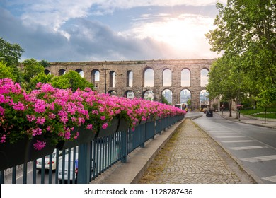 Ataturk Boulevard and Ancient roman Aqueduct of Valens in Istanbul on sunrise and flowers in front